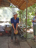 Splitting a coconut - preparation for making coconut candy - on an island near My Tho in the Mekong Delta, Vietnam