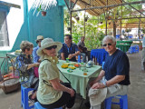 Helen, Janet & Stan at a tea party (with fruit) while musicians played - on an island near My Tho in the Mekong Delta, Vietnam