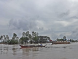A sampan (foreground) on the Mekong River - in Vietnam while traveling by boat from Chau Doc, Vietnam to Phnom Penh, Cambodia
