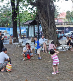 A Cambodian taking photos of his children near the Wat Phnom Temple - Phnom Penh, Cambodia