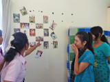 The only wall decor in the room of our sponsored college young ladies - photos of family and friends - Phnom Penh, Cambodia
