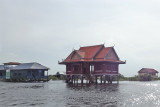Buildings (on stilts/piles) - red one is a temple? - a stilted village on Tonle Sap Lake in the Siem Reap Province of Cambodia
