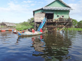 House (on stilts/piles) and boat in a stilted village on Tonle Sap Lake in the Siem Reap Province of Cambodia