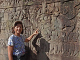 Judy examining the beautiful bas-reliefs on the outer wall of the Bayon Temple in Angkor Thom, Siem Reap Province, Cambodia