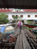 Janet walking on old wooden planks to get back to her boat after leaving the concrete Wildlife Conservation Society building