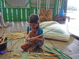 A girl weaving water hyacinths for baskets & place mats sold at a floating gift shop we visited - Tonle Sap Lake