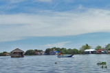A floating house (left) being towed by a boat (right) to another location - Tonle Sap Lake, Siem Reap Province, Cambodia
