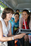 Judy showing photos of her family on her mini tablet to some of our sponsored young ladies (college students) - on our bus