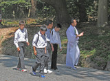 Schoolboys and a monk approaching the Meiji Shrine inner complex on the gravel road entrance surrounded by cedars - Tokyo