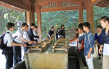 Students engaging in ceremonial purification and cleansing at a temizuya before going to the main shrine at Meiji