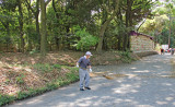 Worker on the gravel road to and from the Meiji Shrine. Sake barrels are in the background on the left side of the road.