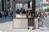 A man who appears to be a monk or priest soliciting donations in Ginza - traditional and modern Japan cross paths
