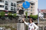 Judy rubbing the belly of Hotei - the potbellied deity of prosperity - at  the Kajibashi Bridge end of the Morning Market.