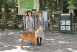 Two women and a deer near the path to Kasuga Taisha (a Shinto shrine) in Nara Park in Nara
