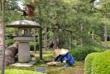 Workers near a traditional Yukimi (snow viewing) stone lantern at the Kenroku-en Garden in Kanazawa