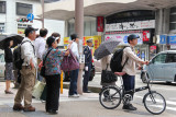 Pedestrians wait for a signal from the man in unform for permission to cross the street - front of the Omi-cho Market in Kanaawa
