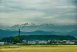 Plains and snow capped Hakusan Mountains seen while traveling from Kanazawa to the Kutani Pottery Village in Nomi-shi