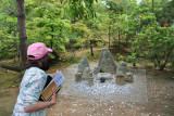 Judy tossing coins at Jizo Buddhist statues for good luck - on the grounds of the Temple complex (Rokuon-ji) in Kyoto