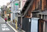 Woman on a bike in a residential neighborhood in Kyoto