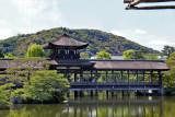 Roofed bridge (Taihei-kaku) over a pond at the garden of the Heian-jingu Shrine in Kyoto (background - Higashiyama Hills)