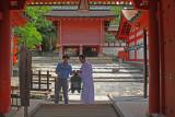 A monk and his assistant hanging a bronze lantern at Kasuga Taisha (a Shinto shrine) in Nara Park in Nara