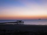 Dawn - Fishing pier and cargo ship - East Coast of Tybee Island