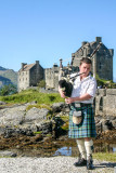 Bagpiper, Eileen Donan Castle in Dornie with Loch Duich, Scotland