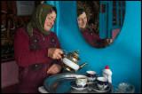 A woman preparing tea in Xinaliq teahouse