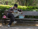 Reading newspaper in a cool park