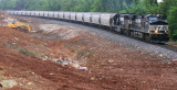 A Northbound grain train passes a crew working drainage for the new roadbed at Jones Knob road