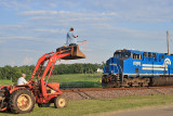 Emmett up in the bucket of a tractor, getting a high shot of the Conrail Heritage engine at Bondville