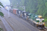SR 8099 leads train 197 through the crossover at Revilo during a strong summer storm