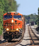 A BNSF swoosh logo GE brings NS 143 down the tangent at Pine Knot
