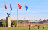 The flags of a veterans memorial fly high as NKP 765 passes in the distance at New Waverly
