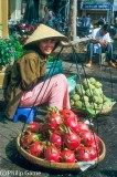 Young woman selling green dragon fruit