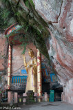 Buddha effigy tucked under a cliff overhang