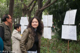 Woman amused by the 'marriage market' posters at Peoples Park