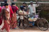 Women gather around a peddler's bicycle