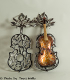 An old violin encased in a metal cage ready for a Symphony fundraiser.