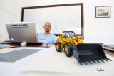 SELFIE WITH AN UWA. My cluttered desk becomes my studio for an experimental selfie session to check how this zoom renders the out-of-focus busy background.  I laid down the camera on the desk with the wide open 16-35 f4 IS, focused on the model payloader via live view (near MFD), then tripped the shutter using the self-timer.  Shooting info - Rosario, La Union, Philippines, May 28, 2015, Canon 5D MIII + EF 16-35 f/4 L IS, 16 mm, f/4, ISO 160, 1/10 sec,  manual exposure in available light, live view AF, self-timer, AWB, uncropped full frame resized to 1500 x 1000 pixels.