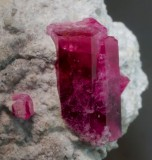 Red beryl, 12 mm long, transparent, on rhyolite, Violet Claims, Wah Wah Mountains, Beaver County, Utah.