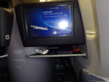 In my cubicle on the plane, with a fold down seat into a bed. My feet rested on the ledge below the monitor.