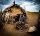 Old Woman outside her hut