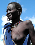 Surma woman with streched lower lip and stretched ear lobes for plates;  south-western Ethiopia.