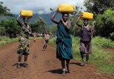 Surma women carrying water canisters;  south-western Ethiopia.