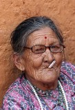 Old lady in Nepal smoking a cigarette