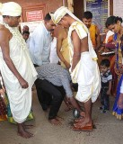 Wedding ceremony in Karnataka, India; a member of the bride's family washes the groom's feet