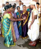 Wedding ceremony in Karnataka, India; female members of the bride's family present a holy flame to the groom