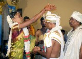 The bride blesses her future husband with some grains of rice; Wedding ceremony in Karnataka, India