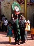 Devotee carrying a basket containing a brass bust of Yellamma, Yellamma temple,  Saundatti, Karnataka, India